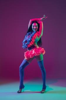 하계. 네온 불빛에 보라색 벽에 하와이 갈색 머리 모델. 웃고, 춤추고, 재미 전통 옷을 입고 아름다운 여성. 밝은 휴일, 축하 색상, 축제.