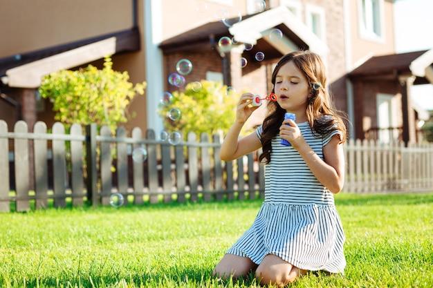 Летнее хобби. красивая маленькая девочка сидит на траве возле своего дома и пускает мыльные пузыри