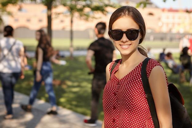 Immagine estiva dell'adolescente adorabile alla moda che indossa occhiali da sole neri e zaino che cammina nel parco cittadino con un bellissimo edificio e persone. donna carina in viaggio