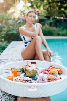 タイでの夏の旅。フォアグラウンドのフローティングテーブルで新鮮なエキゾチックなアジア料理と飲み物。美しい女性がプールの周りでポーズをとる。