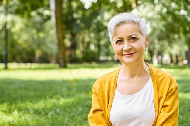 여름철, 성숙한 사람, 나이 및 여가 개념. 미소와 함께 야생의 자연에서 편안한 노란색 카디건을 입고 회색 짧은 머리를 가진 세련된 백인 여자 연금의 야외 촬영