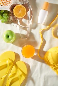 フルーツバッグ、フリップフロップ、sinクリームとジュース、フラットレイと白い背景の上の夏のピクニック