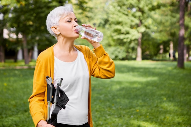 Summertime portrait of tired gray haired caucasian female in her sixties drinking water from plastic bottle, refreshing herself after physical activity, posing outdoors with nordic walking sticks