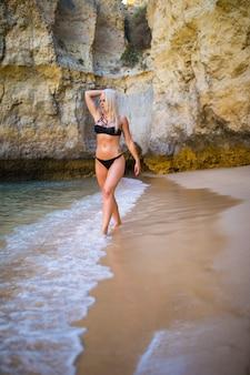 Концепция летнего отдыха. красивая молодая сексуальная женщина с подтянутым натренированным стройным телом в черном купальнике бикини гуляет по пляжу у моря