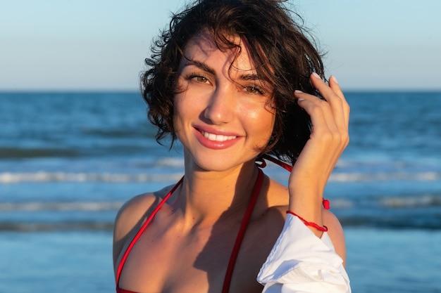 夏のレクリエーションのコンセプト。砂浜で赤い水着ビキニポーズを身に着けているフィットトレーニングスリムボディを持つ美しい若いセクシーな女性。海の近くのファッション女性モデル。