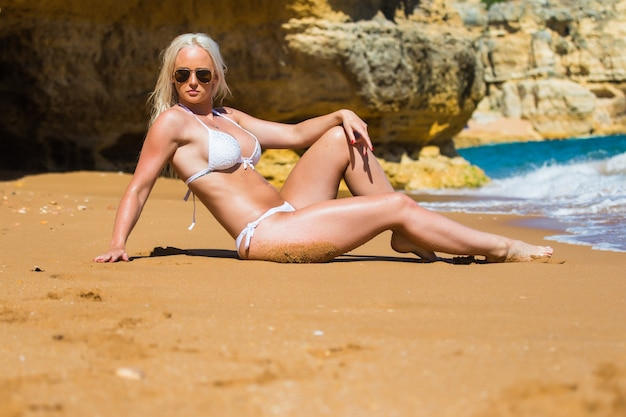 Summertime recreation and travel concept. beautiful tanned young fashion model in bikini posing on the sea coast. woman in beachwear swimsuit with wet hair and body lying on a beach