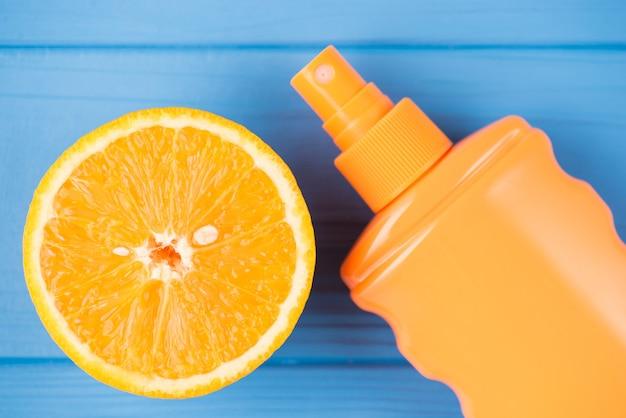 夏のリラックスコンセプト。青い木製の背景に分離されたオレンジスライスとspf日焼け止めの俯瞰写真の上の上
