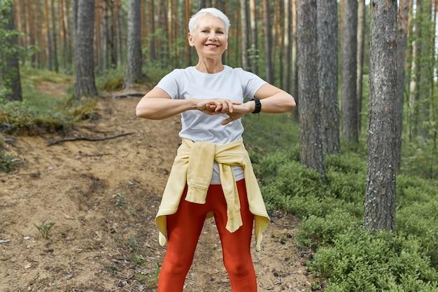 夏、スポーツ、活動、幸福の概念。美しいエネルギッシュな引退した女性が屋外で運動し、走る準備をし、ウォーミングアップし、筋肉を伸ばし、木の間の小道に立っています。