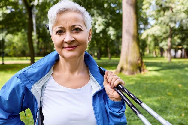 여름철, 스포츠, 레크리에이션, 건강 및 활동 개념. 북유럽 산책을위한 막대기로 숲에서 포즈를 취하는 파란색 재킷에 매력적인 정력적 인 노인 여성의 야외 촬영