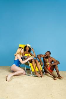 Летняя история. счастливые молодые друзья отдыхают и веселятся на синем фоне студии. концепция человеческих эмоций, выражения лица, летних каникул или выходных. холод, лето, море, океан.