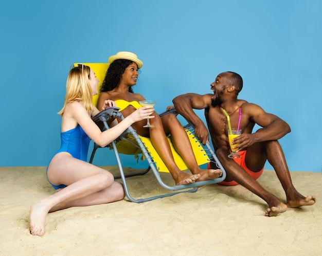 Storia estiva. giovani amici felici che riposano e che si divertono su sfondo blu studio. concetto di emozioni umane, espressione facciale, vacanze estive o fine settimana. freddo, estate, mare, oceano.