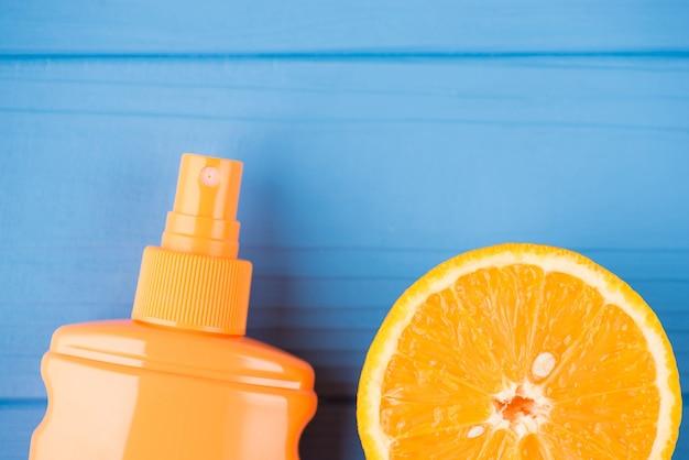 夏の休暇のコンセプト。日焼け止めとコピースペースで青い木製の背景に分離されたオレンジスライスの俯瞰のクローズアップ写真の上の上