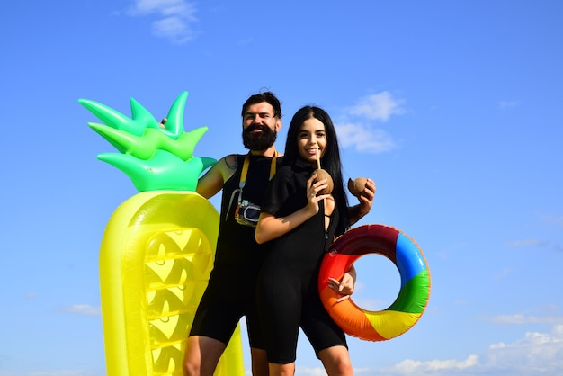Summertime vacation summer couple concept sexy woman in swimsuit and man with inflatable mattress