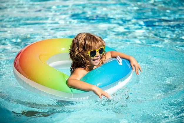 夏休み。夏の子供たちの週末。アクアパークの膨脹可能なゴム製の円のプールの面白い男の子。