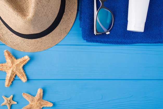 夏の休暇の時間の概念。上の俯瞰図のクローズアップ写真ヒトデタオルサングラス日よけ帽とコピースペースと青い木製の背景で隔離の日焼け止め