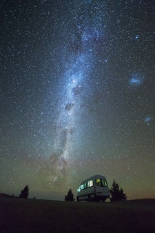 Summertime view of milky way and night sky with camper van at south island new zealand