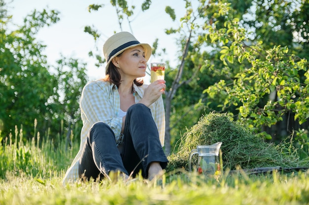 Summertime, woman gardener in hat sitting on freshly cut grass with homemade natural drink mint with strawberries, green garden background
