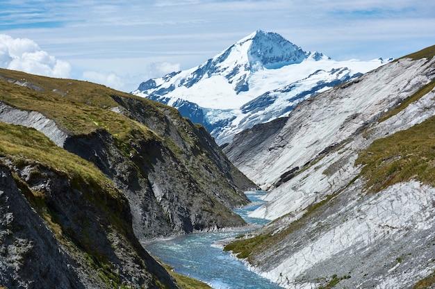 マウント・アスパイアリング山の頂上が狭い峡谷にそびえ立ち、曲がりくねった川が流れています