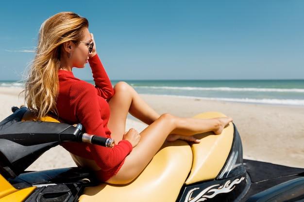 Летнее фото моды сексуальной белокурой женщины в красном обмундировании, сидящей на желтом водном самокате над тропическим пляжем.