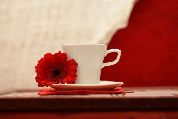 豪華な朝。白いカップ、赤い花、豪華