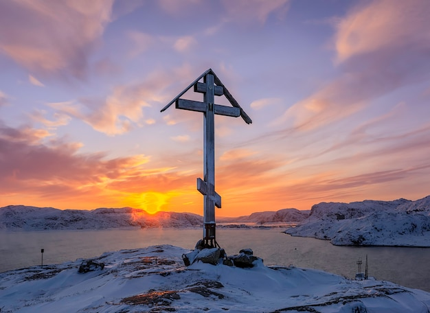 Sun angel over the mount and orthodox cross on the top of the snow capped mountain at sunrise in teriberka, russia