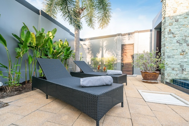 Sun bed with umbrella and green plants in the house or home building