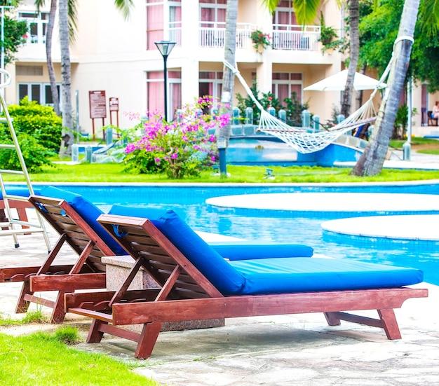 トロピカルリゾートホテルのプールの近くにあるビーチパラソル付きのサンベッドとデッキチェア。