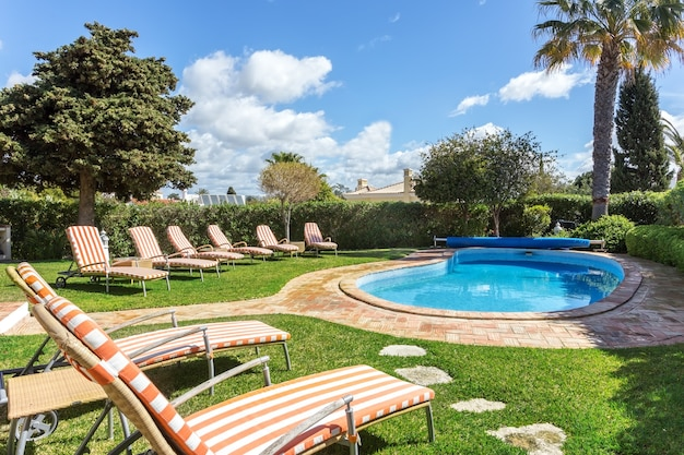 リラックスできる豪華なプールの近くにあるサンベッドとマットレス。