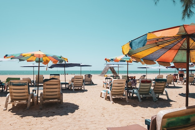 Sun beds on tropical beach with calm sky. sea view and sand beach, summer background.