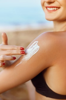 Sun cream. skin and body care. woman in bikini  applying sunscreen solar on tanned  shoulder.