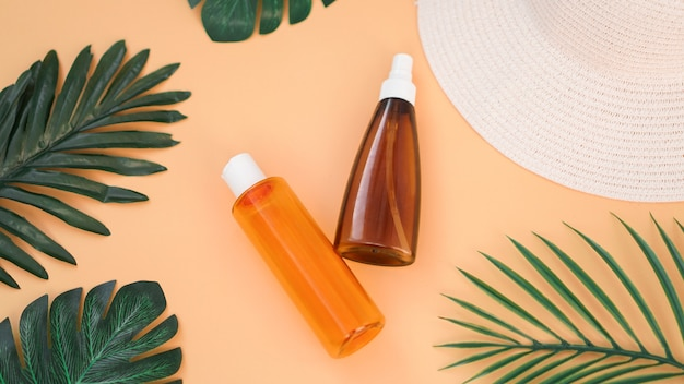 Крем для загара, шляпа от солнца, бутылка лосьона на мягком оранжевом фоне. защита от солнца. летнее время и отпуск