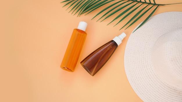 柔らかいオレンジ色の背景に日焼け止めクリーム、日よけ帽、ローションボトル。日焼け止め。夏時間と休日