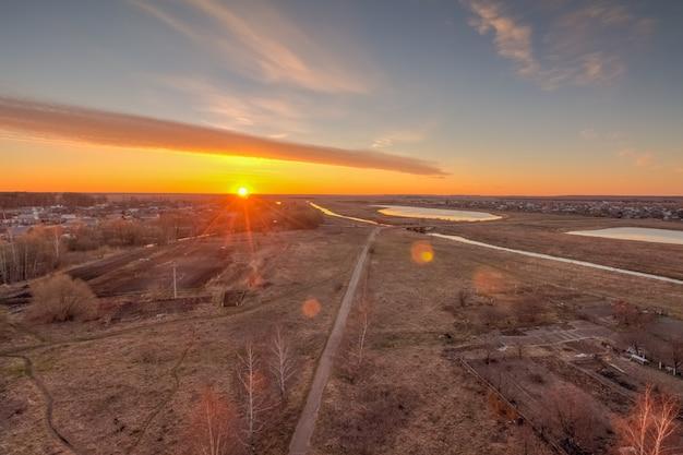 Sun at dawn on the horizon above the village