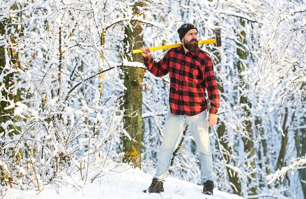 Sun day man with axe in the forest a man in a winter forest lumberjack with an ax in his hands bearded lumberjack