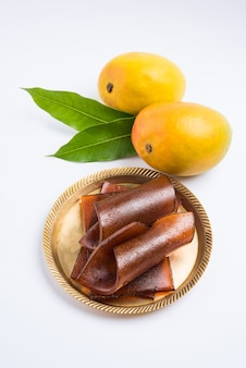 Sun dried aam papad or indian fruit leather made out of mango pulp mixed with concentrated sugar solution. selective focus
