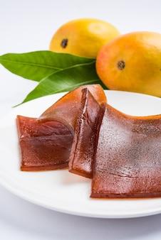 농축 설탕 용액과 혼합된 망고 펄프로 만든 태양 건조 aam papad 또는 인도 과일 가죽. 선택적 초점