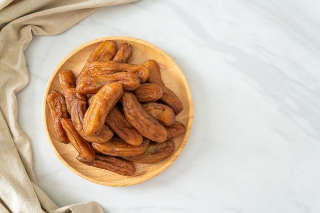 Вяленый банан на деревянной тарелке