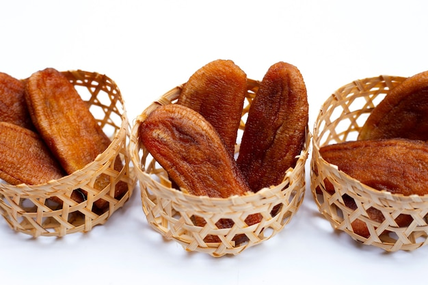 Sun dried bananas in bamboo basket on white background.