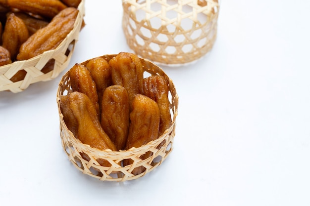 Sun-dried bananas in bamboo basket on white background.