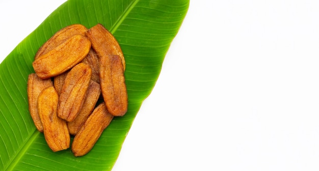Sun dried bananas on green leaf on white background.