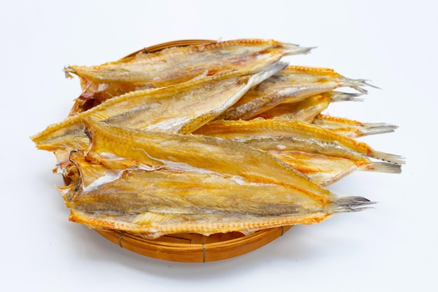 Сушеные на солнце черные королевские рыбы в бамбуковой корзине на белом фоне.