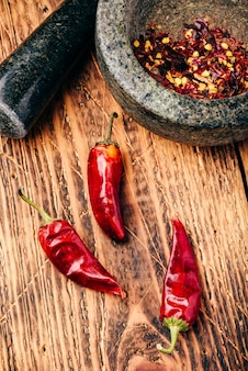 Sun dried red chili peppers on wooden surface with mortar and pestle