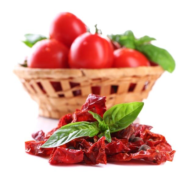 Вяленые помидоры, свежие помидоры в плетеной корзине, листья базилика, на белом
