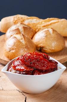 하얀 그릇에 햇볕에 말린 토마토, 백그라운드에서 빵.