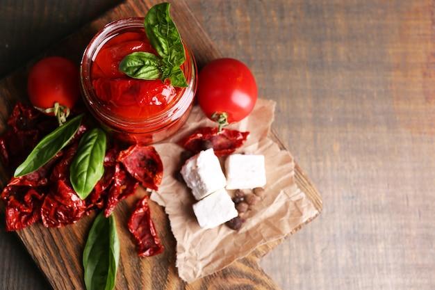 유리 항아리에 태양 건조 토마토, 바질 잎과 나무 표면에 커팅 보드에 죽은 태아의 치즈