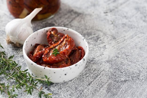 Sun-dried tomatoes in a plate on light concrete