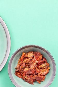 민트 컬러 세라믹 접시에 이탈리아 허브와 향신료와 함께 태양 건조 토마토 조각