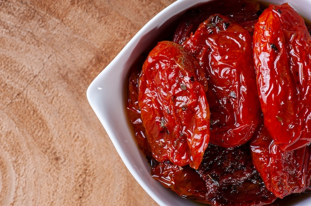 Sun-dried tomatoes in a white bowl on a woody background. top view