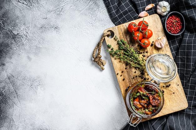 ハーブと塩をグラスにオリーブオイルで乾燥させたトマト。灰色の表面。上面図。コピースペース