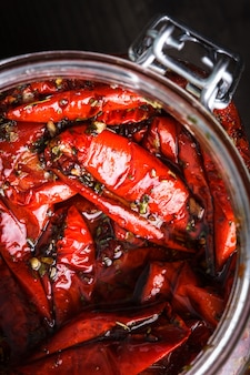 Sun dried tomatoes with herbs and olive oil in jar